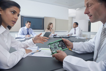 Engineer and businesswoman discussing electronics part in conference room