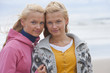 Portrait of smiling teenage twin sisters on beach
