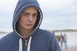Portrait of serious teenage boy in hoody on beach with friends in background
