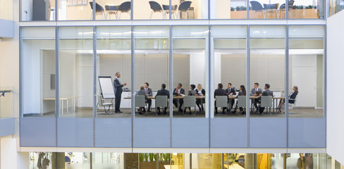 View of business people meeting in conference room from outdoors
