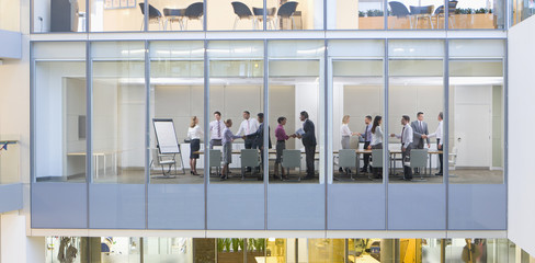 View of business people shaking hands in conference room from outdoors