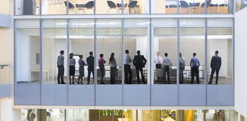 View of business people standing in conference room from outdoors