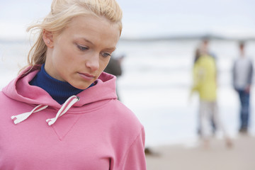 Pensive teenage girl on beach with friends in background