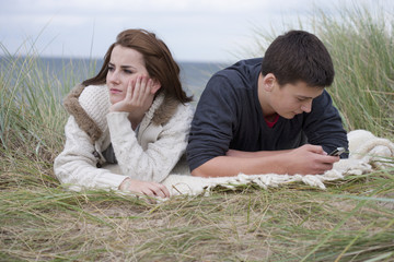 Teenage girl turning away from teenage boy text messaging on cell phone in grass on beach