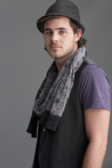 Portrait of smiling young man wearing scarf and fedora