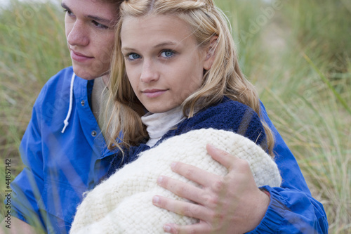 Close up of serious teenage couple hugging in grass