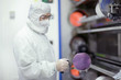 Engineer in clean suit holding silicon wafer in clean room