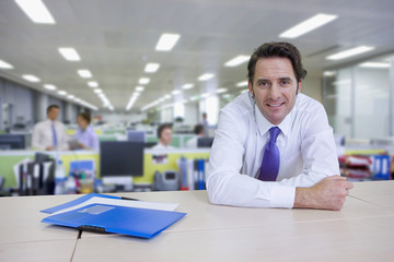 Portrait of confident businessman leaning on cabinet in office