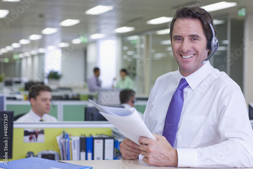 Portrait of smiling businessman wearing headset and reviewing report in office