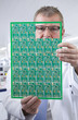 Engineer examining printed circuit board in laboratory