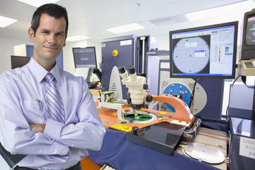 Portrait of smiling businessman in silicon wafer manufacturing laboratory