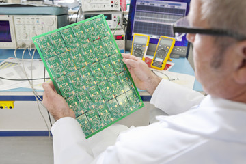 Engineer examining printed circuit board at electrical test bench