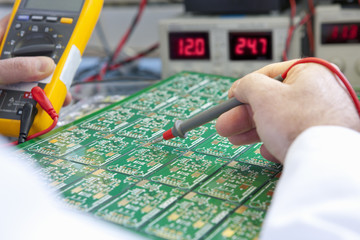 Engineer working on circuit board at electrical test bench