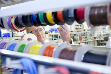 Engineer inspecting vibrant wire spools in laboratory