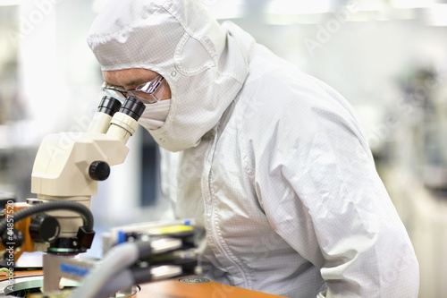 Scientist in clean suit examining silicon wafer in telescope in laboratory