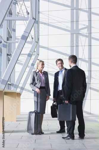 Business people with briefcases and suitcase talking in modern lobby