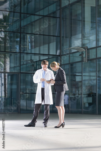 Businesswoman and engineer examining machine part in front of building