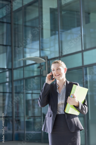 Smiling businesswoman holding binder and talking on cell phone outside building