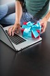typing in laptop with gift box