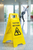 Businessman slipping behind wet floor sign in lobby