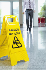 Businessman approaching wet floor sign on lobby floor