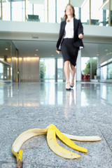 Businesswoman approaching banana peel on lobby floor