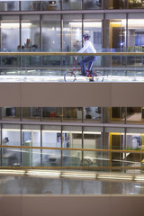 Businessman riding bicycle down office corridor
