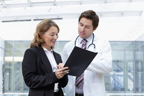 Businesswoman and doctor reviewing paperwork in hospital