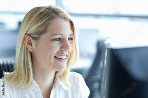Smiling blonde businesswoman using computer in office