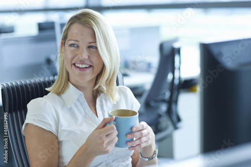 Smiling blonde businesswoman drinking coffee at computer in office