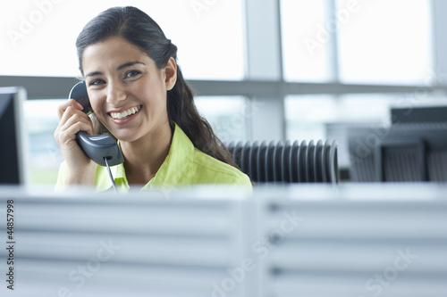 Portrait of smiling brunette receptionist talking on telephone in office