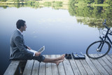 Young businessman using laptop near lake