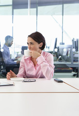 Brunette businesswoman drinking coffee at conference room table