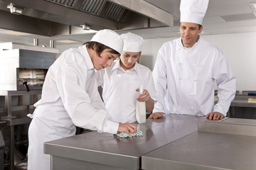 Chef watching trainees cleaning work surface in commercial kitchen