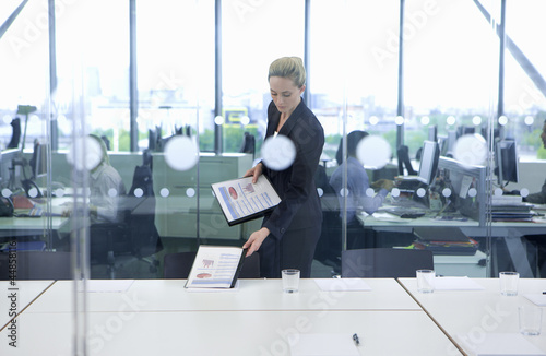 Blonde businesswoman placing packets on table in conference room