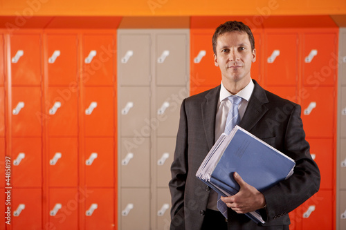 Serious teacher holding paperwork near school lockers