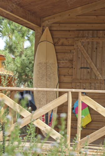 Surfboard leaning against wall of house