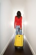 red sweater woman with yellow suitcase