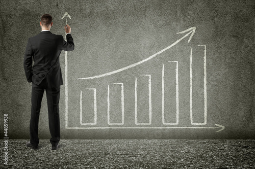 businessman drawing trend chart on wall