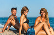 Group portrait of threesome on beach.