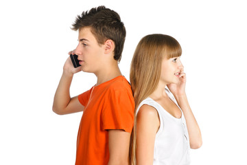 teenage boy and girl chatting on cell phones standing back to ea