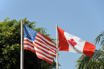 American and Canadian flag waving in the wind