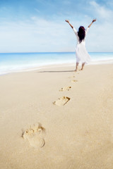 Footprints and carefree woman