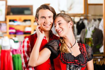 Paar probiert Dirndl und Lederhose in Boutique