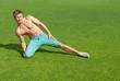 Young man training on green grass