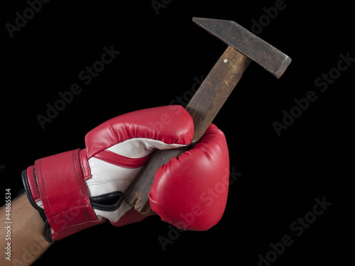 hand in a glove beating a hammer
