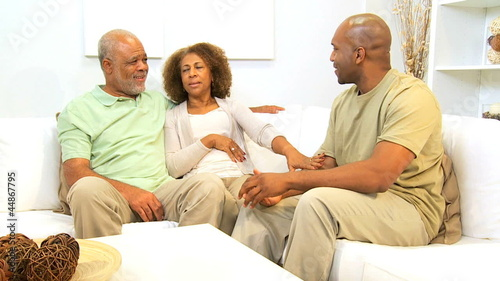 African American Parents Relaxing Son Home