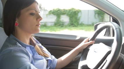 Young pretty businesswoman driving car