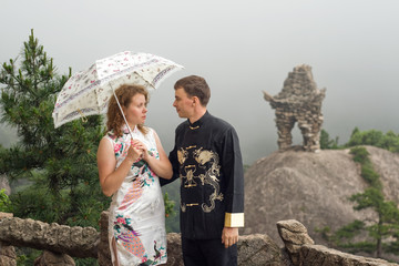 lovely couple with umbrella on Chinese mountain of Huangshan