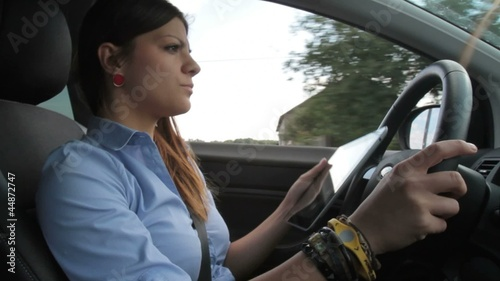 Young pretty businesswoman with tablet driving car